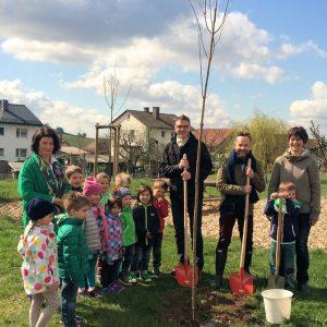 Michael Roth MdB, der Friedewälder Bürgermeister Dirk Noll und die Kinder und Erzieherinnen der KiTa Friedewald freuen sich über den neuen Rot(h)ahorn.